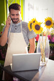 Male florist talking on mobile phone while using laptop Royalty Free Stock Photo