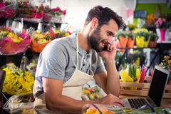 Male florist talking on mobile phone while using laptop Stock Photography
