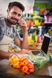 Male florist talking on mobile phone while using laptop Stock Photo