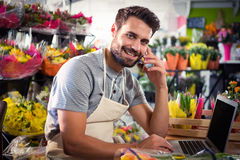 Male florist talking on mobile phone while using laptop Royalty Free Stock Images