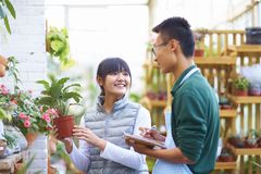 Male Florist Talking to his Customer in the shop. Young Asian Male Florist Have Conversation with his Customer in the Shop Royalty Free Stock Photo