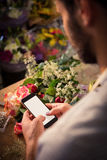 Male florist text messaging on mobile phone. At his flower shop Stock Image