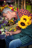 Male florist trimming stems of flowers at flower shop. Male florist trimming stems of flowers at his flower shop stock photography