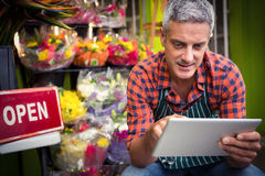 Male florist using digital tablet. At his flower shop Stock Image