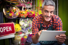 Male florist using digital tablet. Portrait of male florist using digital tablet at his flower shop Royalty Free Stock Photo