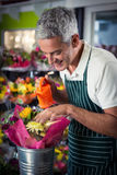 Male florist watering flowers with watering can Royalty Free Stock Photography