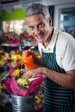Male florist watering flowers with watering can Stock Photos