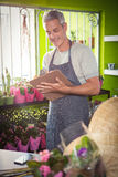 Male florist writing on clipboard Royalty Free Stock Photo