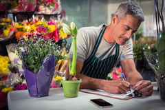 Male florist writing on clipboard Stock Image