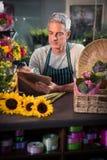 Male florist writing on clipboard Stock Photo