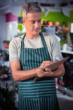 Male florist writing on clipboard. At his flower shop Royalty Free Stock Image