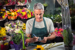 Male florist writing on clipboard. At his flower shop Royalty Free Stock Photography