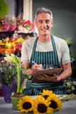 Male florist writing on clipboard Stock Images