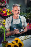 Male florist writing on clipboard. Portrait of happy male florist writing on clipboard at his flower shop Stock Photos