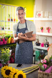 Male florist writing on clipboard. Portrait of happy male florist writing on clipboard at his flower shop Stock Images