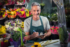 Male florist writing on clipboard. Portrait of happy male florist writing on clipboard at his flower shop Royalty Free Stock Images