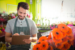 Male florist writing and making notes Royalty Free Stock Image