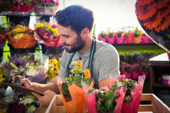 Male florist writing and making notes Stock Photo