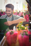 Male florist writing and making notes. At his flower shop Stock Photography