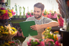 Male florist writing and making notes. At his flower shop Royalty Free Stock Image