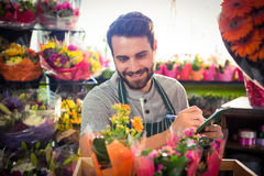 Male florist writing and making notes. At his flower shop Stock Image