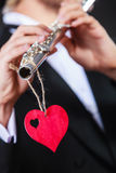 Male flutist with flute and heart. Love melody Stock Images