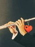 Male flutist with flute and heart. Love melody Royalty Free Stock Images