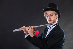 Male flutist with flute and heart. Love melody Royalty Free Stock Image