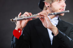 Male flutist with flute and heart. Love melody Royalty Free Stock Photo