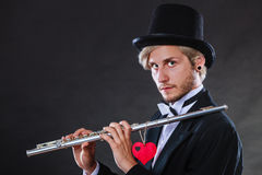 Male flutist with flute and heart. Love melody Royalty Free Stock Photos