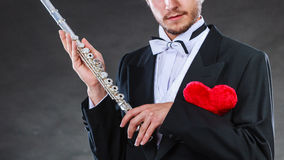 Male flutist with flute and heart. Love melody Stock Photo