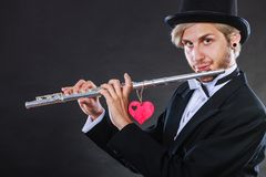 Male flutist with flute and heart. Love melody. Valentines day love melody concept. Flute music playing male flutist musician performer. Young elegant stylish Royalty Free Stock Photos