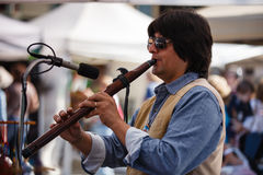 Male Flutist Johnsy G - The Whisper. Flutist performs at Annual Craft Show in historic Occoquan, Virginia.  Johnsy Gonzales, The Whisper, specializes in bamboo Stock Image