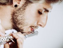 Male flutist playing his flute closeup Stock Images