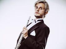 Male flutist wearing tailcoat holds flute Stock Image