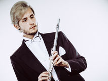 Male flutist wearing tailcoat holds flute Stock Images