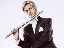 Male flutist wearing tailcoat holds flute Stock Photos