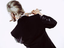 Male flutist wearing tailcoat plays flute Royalty Free Stock Photography
