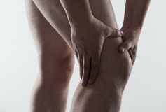 Male foot pain. Closeup of young male massaging his sore knee. Joint disease treatment Royalty Free Stock Images