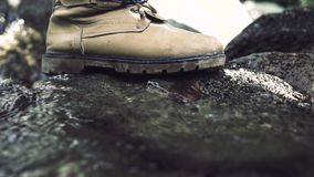Male foot stepping on stone in flowing river. Male foot in shoe walking along rocky mountain river in journey. Travel. Trekking and tourism stock video
