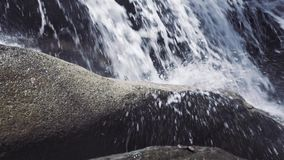 Male foot stepping on stone in flowing river from mountain waterfall. Male foot in shoe walking along rocky mountain. River in journey. Travel, trekking and stock footage