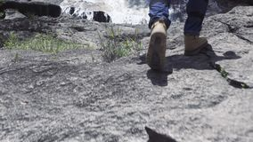Male foot stepping on stone in flowing river from mountain waterfall. Male foot in shoe walking along rocky mountain. River in journey. Travel, trekking and stock video footage