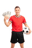 Male football player holding a few stacks of money Royalty Free Stock Photos
