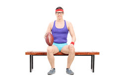 Male football player sitting on a bench Stock Photography