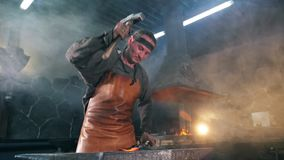 Male forger is striking metal with a hammer in slow motion. HD stock video footage