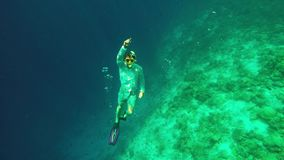 Male free diver coming up to surface during freediving. Lukas is freediving and waving to camera in Maldives stock video