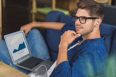 Male freelancer dreaming with laptop on his legs Stock Image