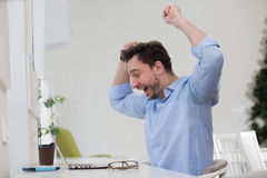 Male freelancer happy. Happy man expressing his positivity with his arms raised. Handsome man in blue shirt looking at laptop computer's screen Stock Photos