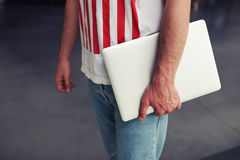 Male freelancer holding close compact laptop computer in the hand. Cropped image male freelancer holding close compact laptop computer in the hand, male student Royalty Free Stock Photo