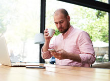 Male freelancer reading text message oh cell phone while working in loft studio Royalty Free Stock Photography